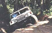 Hummer climbing out of a ditch.