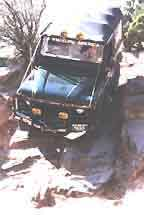 Defender 90 creeping down a cliff in Moab.